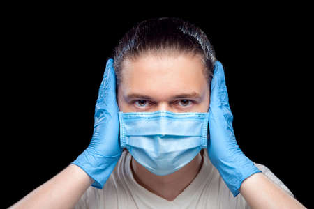 Deaf male portrait of a doctor in a medical mask and surgical gloves covers his ears with his hands so as not to hear anger isolated on a black background concept .