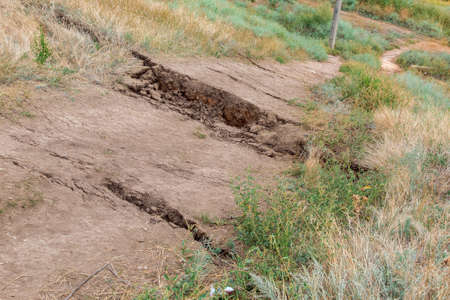 ground trail with cracks in the soil due to a landslide, a close up of a dangerous natural catoclysm, close up nobody.