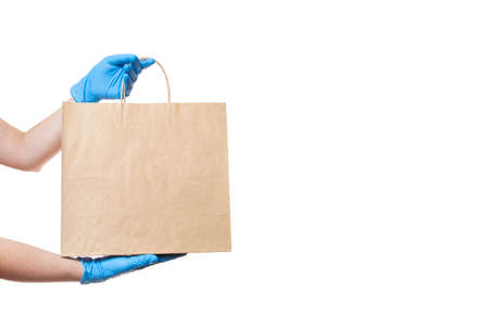 hands in sterile gloves of a courier for the safe delivery of food in eco-friendly craft label package during quarantine of coronavirus covid-19 pandemic isolated on white background with copy space. Banque d'images