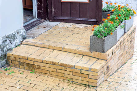 brick threshold with a step at the open wooden entrance door with gray stone flowerpots for flowers, a closeup of architectural details.