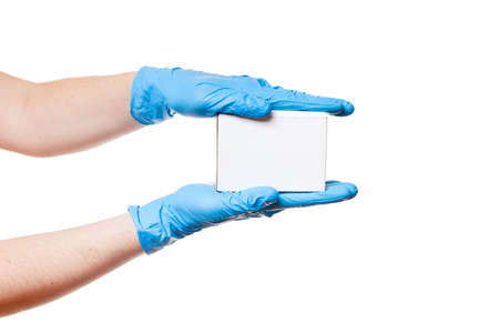 Delivery hands in blue sterile latex gloves holds white un label cardboard box, safe delivery during quarantine of coronavirus covid-19 stay home, concept isolated on white background with copy space. Foto de archivo