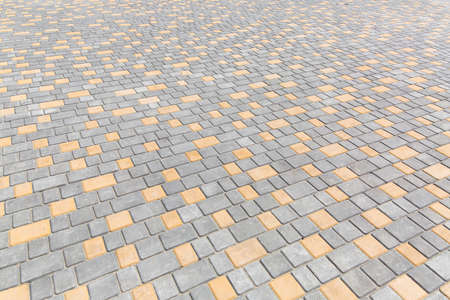paving stone tiles of square and rectangular shape of gray and yellow are paved in perspective, closeup of the road surface.