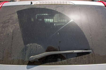 back window of a dirty car covered in dust in a dry mud rear view of a 4x4 suv car, close up nobody.