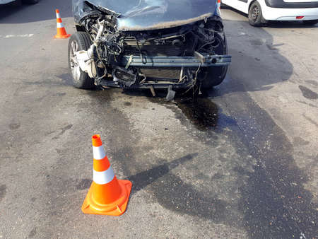 broken suv car after front collision damaged engine compartment of vehicle fenced by orange traffic cones drips of spilled oil from engine, nobody accident frontal impact.