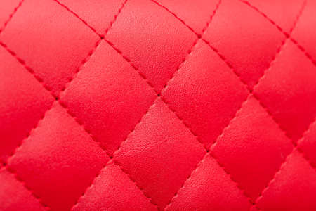 red leather pattern stitched squares with thread seam, decorative texture of animal skin, side view. Banco de Imagens