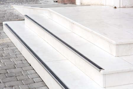 entrance with a marble threshold with stone steps and a white ramp to the exterior on the streets with a pavement of gray tiles. Imagens