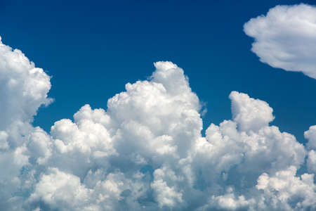 Large white clouds against the blue sky, a natural phenomenon of the weather before the rain. Zdjęcie Seryjne