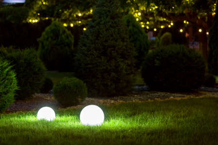 backyard ground light garden with lantern electric lamp with sphere diffuser in green grass and garland bublb on thuja bushes with stone mulching in park with landscaping, closeup night scene nobody. Zdjęcie Seryjne