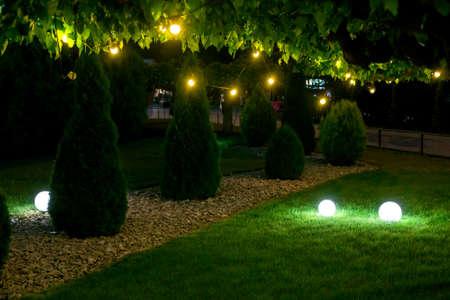 evening illumination backyard light garden with electric ground sphere lantern with stone mulch and thuja bush in landscaping park with garland of warm light bulbs, dark illuminate night scene nobody. Zdjęcie Seryjne