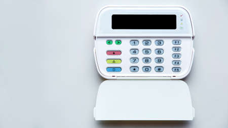Fire Alarm System Control Center with open lid for entering security password and mode settings, front view of device with display and color buttons mounted on light wall with copy space.