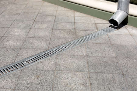 engineering structure downspout on facade building with drainage grate of a gray stone granite sidewalk from square tiles on floor, closeup details city infrastructure, nobody. Stock Photo