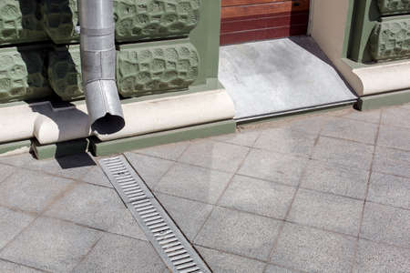 urban engineering structure downspout on green facade building with drainage grate of gray stone granite sidewalk from square tiles with copy space, closeup details city infrastructure, nobody.