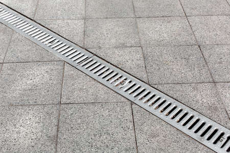 Trench drain gray with steel purification grate on granite stone tile road improvement of the city, close up details drainage system, nobody.