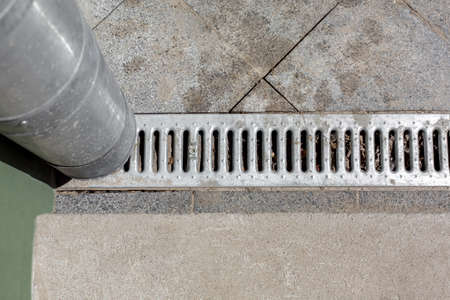 urban engineering structure drainpipe with a drainage grate for drainage of rainwater against a background of a stone granite sidewalk from square tiles, top view.