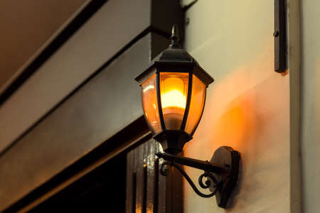 black iron lantern in retro style illuminates wall of building facade with wooden entrance door warm glow light, closeup of lighting fixture side view, nobody. Zdjęcie Seryjne