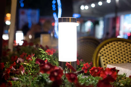 modern steel lantern with a white shade in a flowerbed with red flowers on the terrace of a street city restaurant night glow scene, nobody. Zdjęcie Seryjne