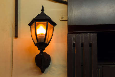 black iron lantern in retro style illuminates wall of building facade with warm glow light, closeup of lighting fixture, nobody. Zdjęcie Seryjne