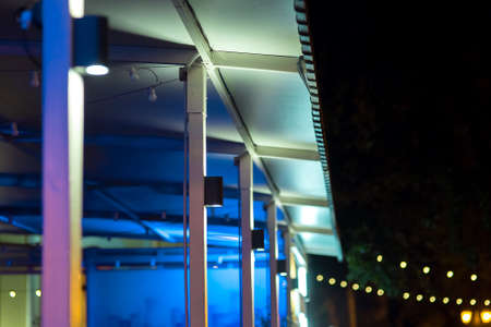 lanterns illuminating the canopy of the outdoor restaurant backyard terrace with modern lamps glow on white gazebo beams shine at night, nobody.