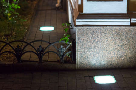Built in grounding lantern in stone tile sidewalk illuminate granite facade of corner architectural building on backyard with iron forged fence, square lamp of street lighting at night, nobody.