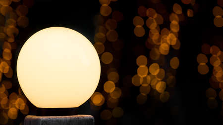 round white street lamp shines with warm glow, in background bokeh diffuse circles from garlands at night on dark background, holiday postcard with copy space.
