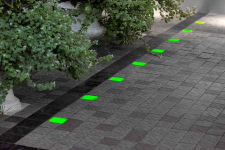 pedestrian walkway of stone tiles with square green ground lanterns set into the floor in a backyard with pots of deciduous plants, built in floor lamps.