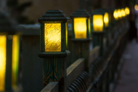 wooden street lamps with yellow glass diffuser on wooden fence of backyard, old light pole glow warm at evening closeup in perspective, nobody.