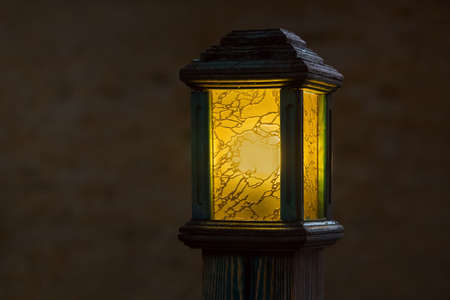wooden street lamp with yellow glass diffuser, old light pole glow warm at evening closeup with copy space, nobody.