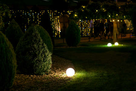 illumination landscape light park with electric ground lantern with round diffuser lamp with garland of light bulbs on background, dark landscaping with illuminate night scene.