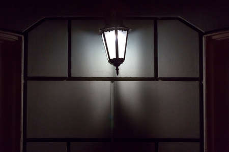 black iron retro lantern with glass hanging on the wall of the facade of the building illuminating the architecture of the city at night, closeup glow detail front view, nobody. Zdjęcie Seryjne