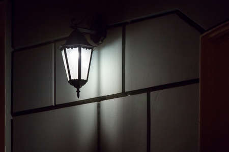 black iron retro lantern with glass hanging on the wall of the facade of the building illuminating the architecture of the city at night, closeup glow detail side view, nobody. Zdjęcie Seryjne