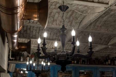 black iron chandelier in retro style with candle-shaped light bulbs on the loft-style brick ceiling near the copper ventilation pipe of the restaurant close-up of the interior, nobody. Zdjęcie Seryjne