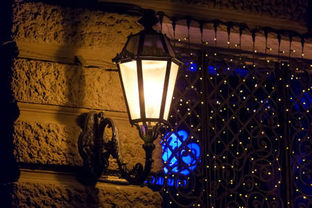 black wrought iron lantern with frosted glass shines with warm light on the facade of a historic building with rustication, in the background a gate with a garland on a dark night close-up, nobody. Zdjęcie Seryjne