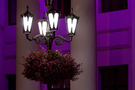 iron retro lantern with wrought iron patterns and hanging flower pot with blooming flowers, street lamp post with quarter lamp illuminates night facade of building with architectural columns. Zdjęcie Seryjne