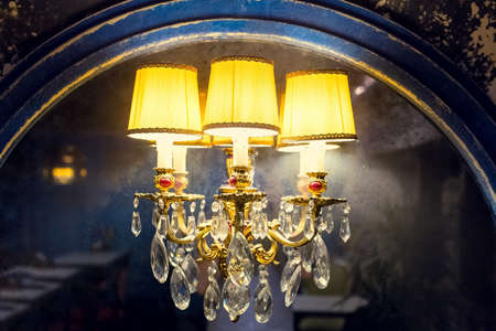 a candelabrum with a yellow lampshade with glass elements on an old mirror with a worn wooden frame, a wall lamp in a dark retro interior shines with warm light closeup front view, nobody. Zdjęcie Seryjne