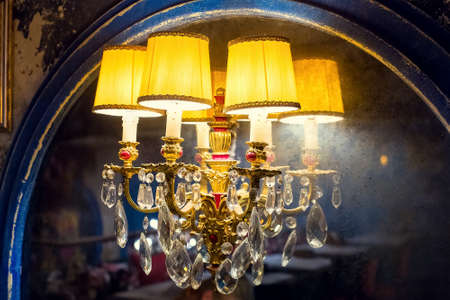 a candelabrum with a yellow lampshade with glass elements on an old mirror with a worn blue wooden frame, a wall lamp in a dark retro interior shines with warm light closeup side view, nobody.