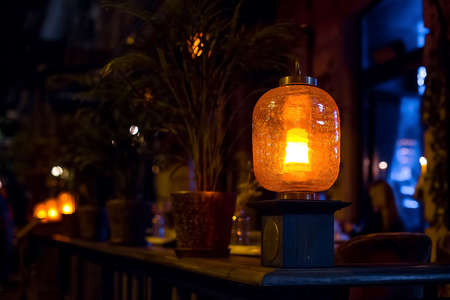 orange glass lantern decorated with cracks installed on the wooden railing of the terrace of a city restaurant with flowerpots, night scene illumination of a cafe, nobody.
