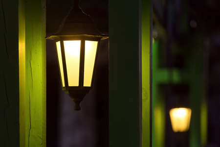 iron classic hanging lantern with frosted glass and warm light in a gazebo with green wooden pillars, lighting fixture closeup night scene, nobody.
