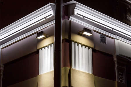 lanterns illuminate details of architectural elements of sculpting of the facade of the building, the volumetric details of the exterior of corner of building with storm pipe night scene, nobody.