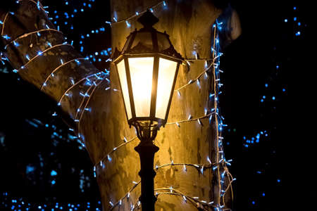 iron retro lamp post shines with warm light by the tree trunk with garland and blue bulbs, forged lantern with frosted glass closeup, nobody.