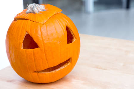 pumpkin with a carved hole for a scary lantern in the form of a head is a symbolic object for Halloween celebration decor on table with copy space, nobody. Zdjęcie Seryjne