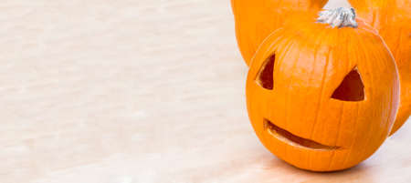 pumpkin with a carved eyes and mouth for a scary lantern in the form of a head is a symbolic object for Halloween celebration decor on table, banner with copy space, nobody.