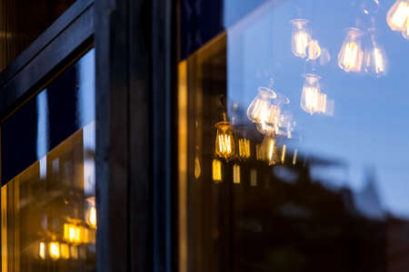 Edison lamps shine a warm light in the restaurant room behind the glass, the details of the cafe lighting through the glass with reflection and glare in the evening, nobody. Zdjęcie Seryjne