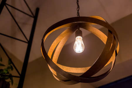 pendant chandelier with wooden circles in the form of a ball with a luminous Edison bulb glowing with warm light, close-up in the evening interior of a cafe, nobody. Zdjęcie Seryjne