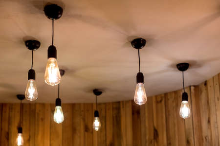 many edison bulbs hanging on a white ceiling in a room with wooden walls, retro style electric lighting in an eco friendly interior close-up of glow details, nobody.