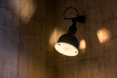 an old industrial lantern with an iron body and frosted glass in an interior with stone walls, an object of wall lighting shines with tempera light in an evening room, nobody. Zdjęcie Seryjne