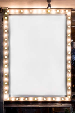 wooden frame with light bulbs illuminating a white canvas on cafe facade building, mock up banner with empty copy space, nobody.