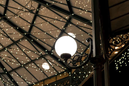 white round lantern on a wrought iron pillar of the restaurant terrace gazebo with garlands on the ceiling, architectural lighting of the room in a retro style, nobody.