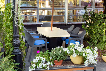 table with wicker chairs in the backyard terrace of an outdoor restaurant with green plants at the front of a building with wooden window frames, nobody.