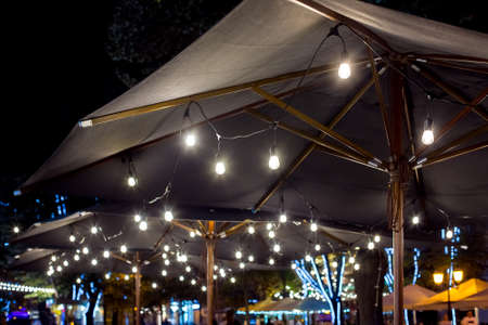 textile umbrella with a wooden frame and edison pendant lamps glowing with light on a backyard terrace night scene, nobody.