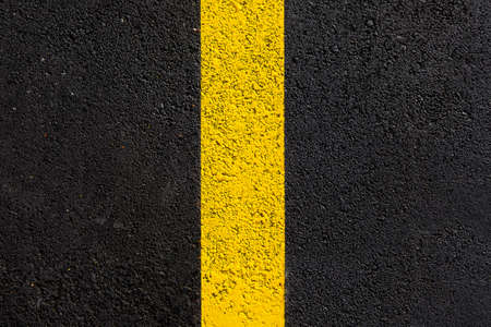 texture tarmac highway road surface with yellow marking smooth dark gray asphalt with copy space close up top view, nobody. Foto de archivo
